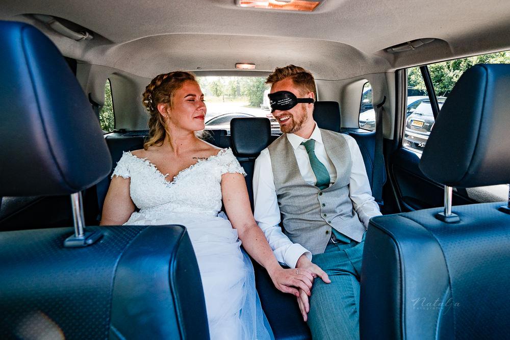 geblindoekt in de auto bruidspaar